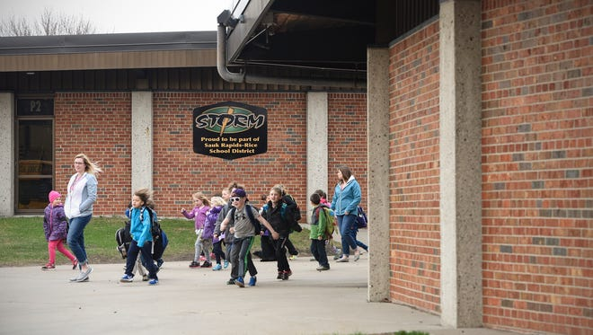 Students walk out the front school doors to board buses for home Thursday, April 13, at Pleasantview Elementary School in Sauk Rapids.