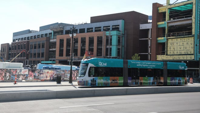 A QLINE car drives by a section of the Little Caesars Arena in downtown Detroit on Woodward on June 12, 2017.