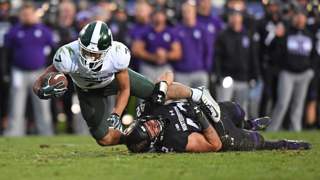 Northwestern linebacker Paddy Fisher tackles Michigan State receiver Cody White during the second half at Ryan Field on Saturday.