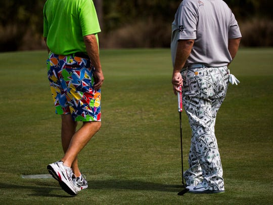John Daly, right, stands by the green, watching other