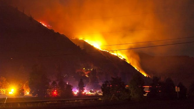 In a Tuesday, Aug. 5, photo, a wildfire sweeps east from the west end of Rowena, threatening homes in Rowena and on the crest above. With steep terrain, high temperatures and high winds, firefighters in the Columbia Gorge are facing a difficult challenge.