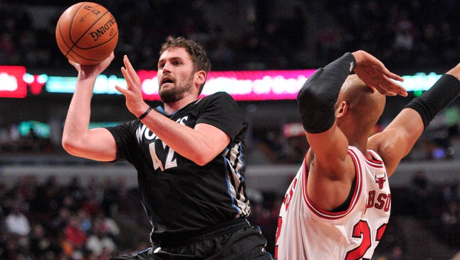 Minnesota Timberwolves power forward Kevin Love shoots the ball past Chicago Bulls power forward Taj Gibson during the second half at the United Center.
