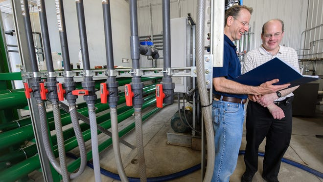 Jim Wallace and Steven Safferman are shown at a dairy farm where they have helped to convert manure into clean water in a project for Michigan State University.