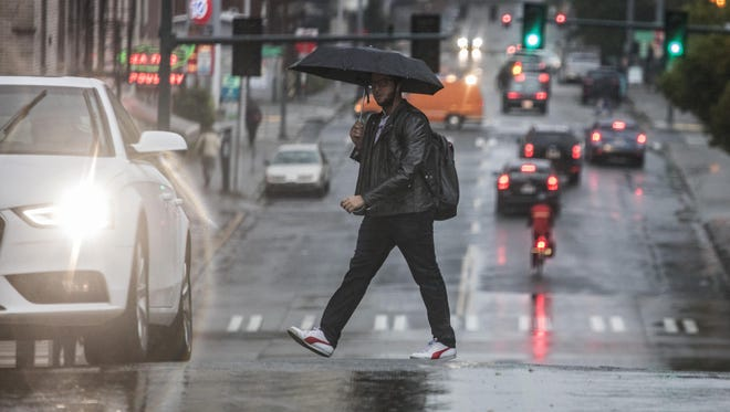 A man walks in the intersection along 15th Ave. NE near the University of Washington campus Thursday, Oct. 13, 2016 in Seattle. The moderate-to-heavy rains Thursday kick off a stormy period - with a lull predicted Friday before the weather intensifies again Saturday. Later Thursday gusts of up to 65 mph are predicted along the coasts.