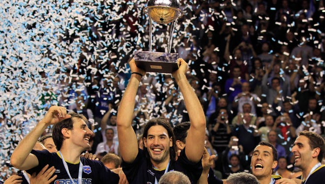 Argentina's Luis Scola, center, holds up the first place trophy as he and teammates celebrate their 80-75 victory over Brazil in last year's FIBA Americas Championship final.