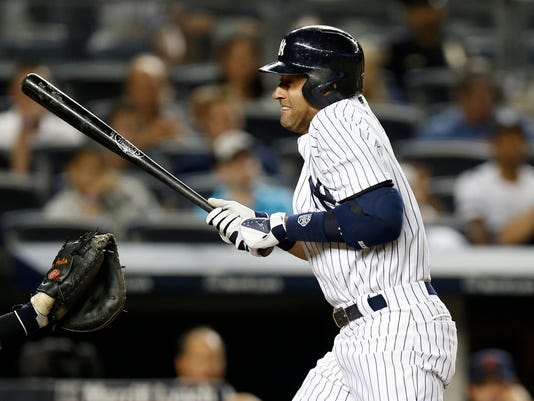 New York Yankees' Derek Jeter reacts as he is hit by a pitch from Detroit Tigers relief pitcher Joba Chamberlain in the 10th inning of a baseball game at Yankee Stadium in New York, Tuesday, Aug. 5, 2014.  (AP Photo/Kathy Willens)