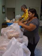 The Machados start setting the food in the backroom of the church. In a few hours, they will give the food to people in need.