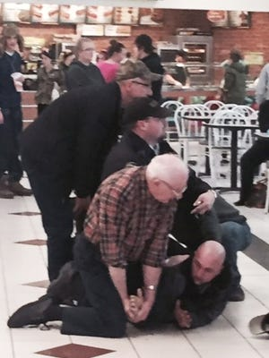 In a Saturday, Feb. 7, 2015, photo provided by Sen. Camera Bartolotta, 75-year-old Charlie Burton, bottom left, of Fombell, Pa., helps tackle shoplifting suspect Jonathan Fekete Jr., bottom right, at the Washington Crown Center mall in Washington, Pa. Burton says he was a vendor at the Washington Crown Center mall for a gun show when he saw an officer struggling with the suspect, 29-year-old Fekete Jr. Police say Fekete was trying to get away after taking $200 worth of clothes from a Macy's store Saturday. Burton says he ran over to help, grabbed the man's arms and forced him down.  (AP Photo/Camera Bartolotta)