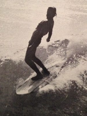 A surfer rides the waves off Pensacola Beach in the 1960s.