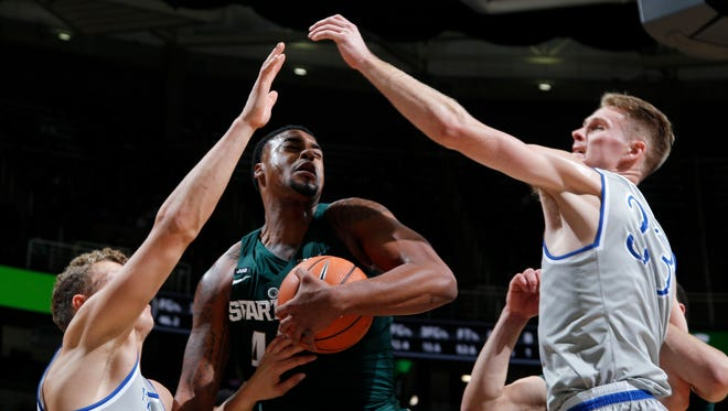 Michigan State's Nick Ward, center, grabs a rebound between Hillsdale's Noah Kalthoff, left, and Gordon Behr during the second half of an NCAA college basketball exhibition game, Friday, Nov. 3, 2017, in East Lansing, Mich.