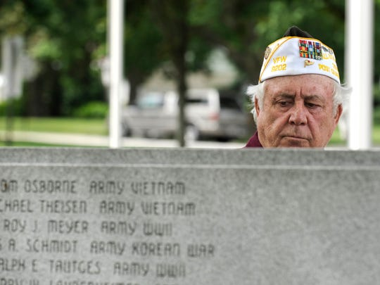 Darrell Brown, a Navy and Army veteran who served two years in Vietnam, looks over the names on a monument at Germantown's Firemans Park on Memorial Day, May 27, 2012. Brown, of Germantown, was at the park for a color guard ceremony and reading of the names on the wall.