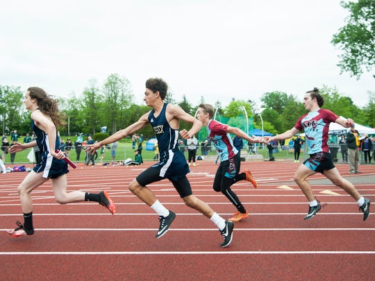 Boys hand off the baton during the 4x100 relay race during the division I high school track and field state championships at Burlington High School on Saturday June 3, 2017 in Burlington. (BRIAN JENKINS/for the FREE PRESS)