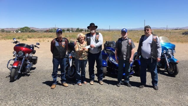 Over the Hill Motorcycle Club members Bill Evans, Bob Clark, Randy LeBelloe and Charles Moore present Silver Stage Food Pantry Manager Kathy McIntosh with a  $500 check.