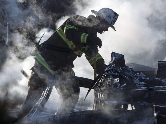 A firefighter picks up debris left from a workshop