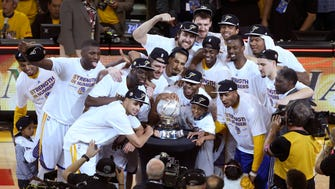 Golden State Warriors players celebrate with the western conference championship trophy after defeating the Houston Rockets in game five of the Western Conference Finals of the NBA Playoffs at Oracle Arena.