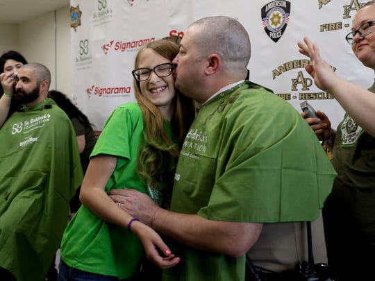 Shasta County sheriff's deputy Tim Wiley gives his 11-year-old daughter, Lola, a kiss after Wiley had his head shaved Friday at Signarama in Redding. Wiley organized the fundraiser for the St. Baldrick's cancer research foundation after a similar event was held on behalf of Lola, who's in remission after fighting leukemia.