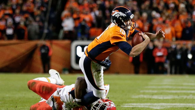 Denver Broncos quarterback Trevor Siemian (13) is pulled down by Kansas City Chiefs outside linebacker Justin Houston (50) in overtime at Sports Authority Field at Mile High.