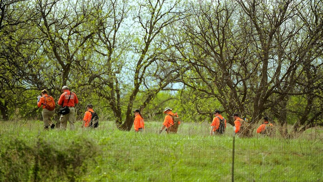 Members of Texas Search and Rescue search a field off Old Anson Road on Saturday in connection with the 2013 disappearance of Clay Rodman.