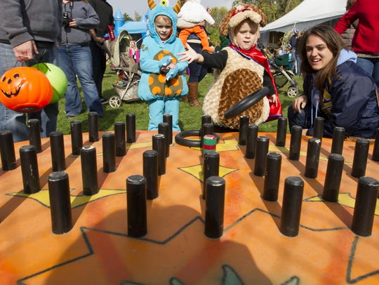 Chlldren play a ring toss game at Zooloween Boo in