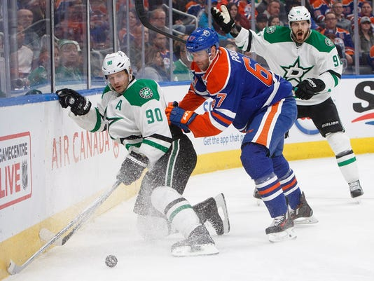 Dallas Stars' Jason Spezza (90) is checked by Edmonton Oilers' Benoit Pouliot (67) during first period NHL hockey action in Edmonton, Alberta, Tuesday, March 14, 2017. (Jason Franson/The Canadian Press via AP)