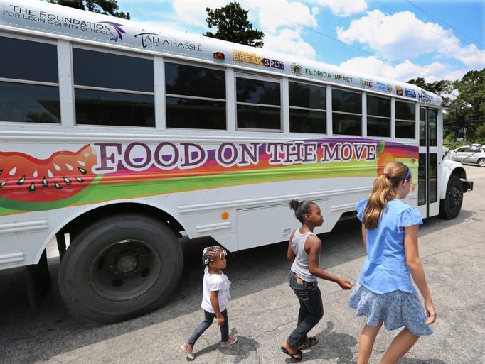A trio heads for the food bus for their Friday lunch. Children living in some of Tallahasseeâ??s poorest neighborhoods are getting food directly to them during the summer with the â??Food on the Moveâ? bus. Whole Child Leon is distributing the food while also doing an assessment survey of the dire needs and determine ways to fill in the gaps. The bus goes to several areas such as Frenchtown and South City. Children in the Griffin Heights Apartments, 1010 Basin St., got a visit from the food bus on Friday, August 1, 2014.