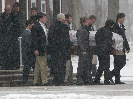 Relatives and friends carry the casket of Madison Stacy