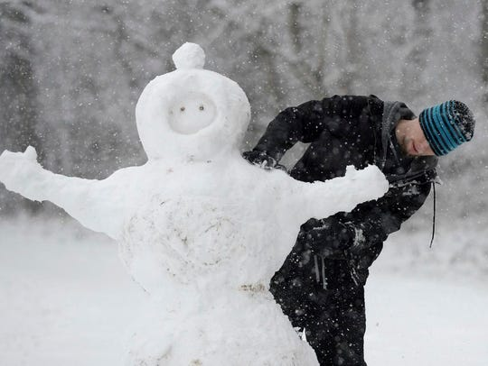Aaron Pearce builds a snowman on Wednesday, Jan. 17,
