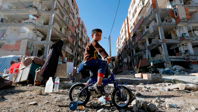 A boy rides a bicycle through the rubble past damaged buildings in the town of Sarpol-e Zahab in Iran's western Kermanshah province near the border with Iraq following a 7.3-magnitude earthquake that left hundreds killed and thousands homeless two days before.