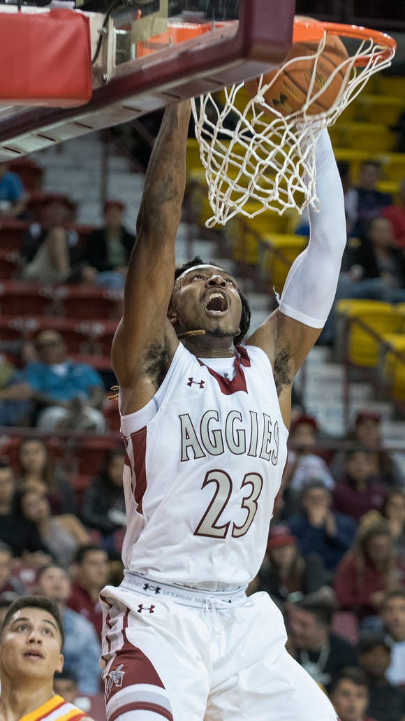 New Mexico State's Marlon Jones gets the dunk on the fast break after getting past Arizona Christian's Matt Willkomm Friday night at the Pan American Center.