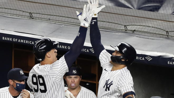 The Yankees' Aaron Judge (99) celebrates with Giancarlo Stanton after hitting a two-run home run in the eighth inning against the Red Sox, as New York came from behind for a 9-7 triumph on Sunday.