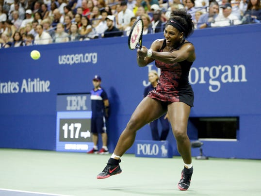 Serena Williams returns a shot to Venus Williams during Tuesday's quarterfinal match at the U.S. Open in New York.