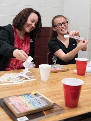 """Alyssa Madden, right, shows off one of her favorite quotes from her """"I Am"""" cup Thursday afternoon at the Pike County YMCA."""