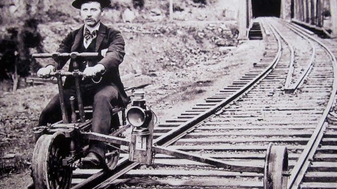 A velocipede is used by a track inspector, who typically worked alone. Made mostly of wood, it was light enough to be easily removed from the track by one person when necessary.