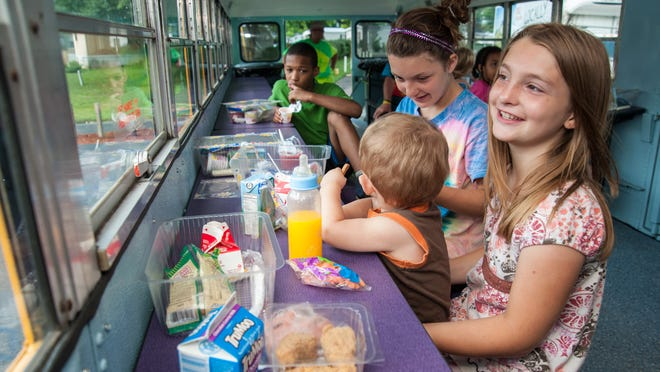 J'Lynn Hudson, 9, far left, watches as Jasmine Walls, 11, and Jayda Walls, 9, feed their 17-month-old stepbrother, Travis Scott, inside the Jefferson County Schools' new Bus Stop Cafe bus during a stop in the Autumn Lake Mobile Home Estate in Valley Station. July 2, 2014