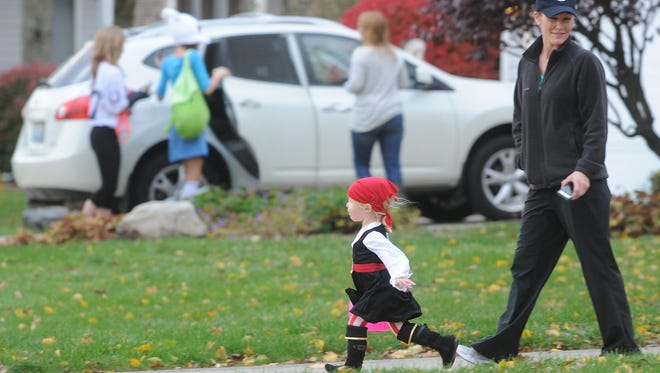 Kids walk to another door while trick-or-treating in Richmond.