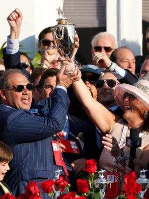 Ahmed Zayat, owner of American Pharoah, and his team hold up the Kentucky Derby winning trophy Saturday afternoon.