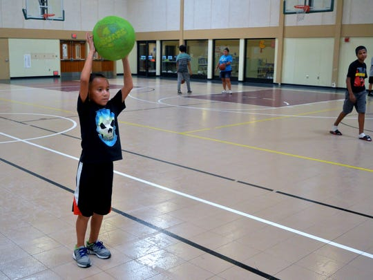 In this archive program, Adrian Suarez bounces a ball with a partner on Tuesday at the Tulare Boys and Girls Club.