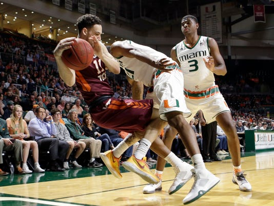 Virginia Tech guard Devin Wilson (11) is fouled by Miami forward Kamari Murphy (21)  during the first half of an NCAA college basketball game,  Wednesday, Feb. 17, 2016, in Coral Gables, Fla. (AP Photo/Alan Diaz)