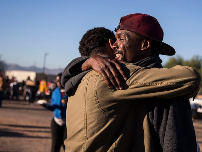 Tyrelle Jackson (left), who is homeless, hugs volunteer