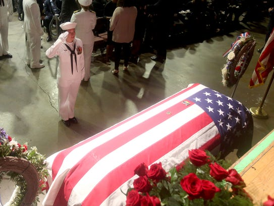 A sailor salutes the casket of Corey Ingram before