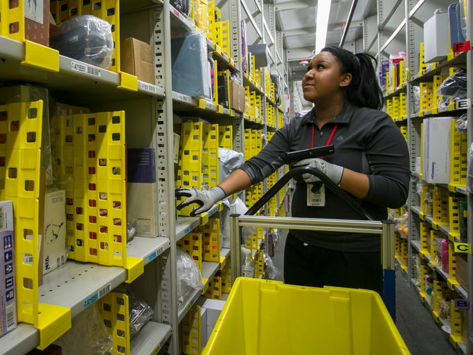 Venessa Williams looks for an item to fill a customer's order at one of the four Amazon fulfillment centers in Phoenix.