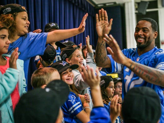 Detroit Lions safety Tavon Wilson high fives children