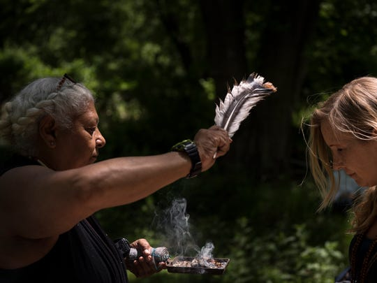 Happy Wonderer, left, burns sage in a practice called smudging, which is said to clear away negative energy, before the start of a Unity and Tobacco Ceremony on Sunday at Split Rock Sweetwater Prayer Camp, where the Ramapough-Lenape Nation has been ordered by the township of Mahwah to remove tepees from the land.