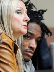 Defense attorney Rhonda Lee, left, sits with her client