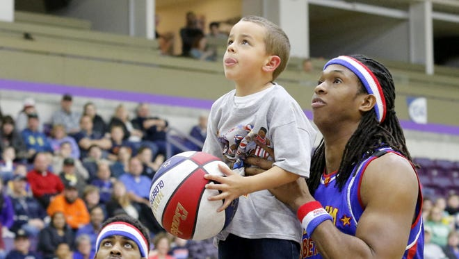 Harlem Globetrotter player Stretch Middleton give's Elmira's Zeri'miah Wilson a hand in making a basket Thursday at First Arena.The Harlem Globetrotters showcase their comedy-filled brand of basketball after their scheduled Feb. 3 appearance at First Arena was postponed because of a slick court. For more photos and video of their performance, visit stargazette.com.