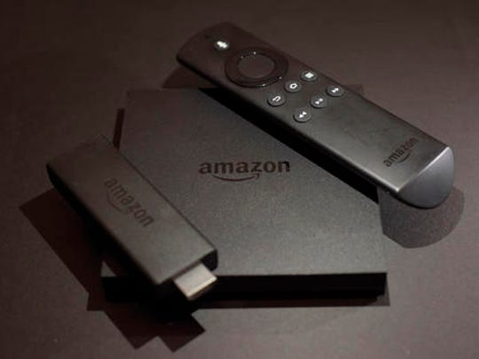 This Wednesday, Nov. 16, 2016 photo shows the Amazon Fire TV, center, and Fire TV Stick, left, streaming TV devices in New York. Your streaming TV options just got better and cheaper. Features that once required a $100 device can now be had for as little as $30. A cheap device is fine for getting TV shows and movies from most popular services onto a big-screen TV, as long as it's a regular, high-definition set.
