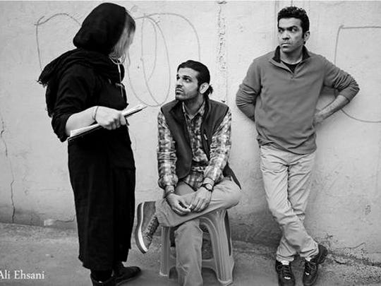 "In this undated photo provided by Iranian filmmaker Keywan Karimi, Karimi, middle, speaks with his script supervisor during a scene of the movie called ""Drum"", Tehran, Iran. Iranian filmmaker Keywan Karimi's production company says he has begun serving a year-long jail sentence handed down over footage deemed insulting by authorities."