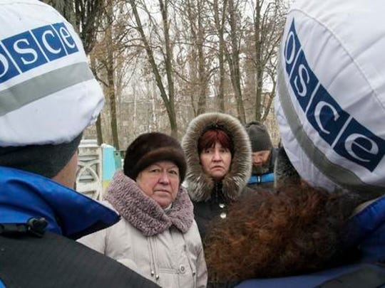 Local residents speak with OSCE monitors in Avdiivka, eastern Ukraine, Friday, Feb. 3, 2017. Strong shelling hit both government- and rebel-controlled areas of eastern Ukraine in a continued escalation of fighting. International monitors issued a sharp call for both sides to still their guns.