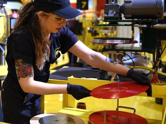 Alejandra Billegas, of Detroit, presses The White Strips 'De Stijl' album during Third Man Records Cass Corridor grand opening of the pressing plant to the public, Saturday, Feb. 25, 2017 in Detroit. Detroit-raised rocker Jack White is building on a vision to blend music and manufacturing in a part of his hometown that long inspired him. The Grammy-winning singer, songwriter, guitarist, drummer and producer is overseeing the launch of a vinyl record pressing plant in the back of his Third Man Records shop north of downtown Detroit.