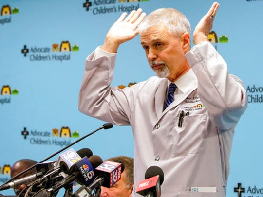 Pediatric neurosurgeon John R. Ruge, MD, describes the surgery during a news conference, Tuesday, March 21, 2017, at Advocate Children's Hospital in Park Ridge, Ill. Ten-month-old Dominique was born in the Ivory Coast with a parasitic conjoined twin. The bottom half of the not-fully-developed twin's body protruded from her neck and back until last week's operation.